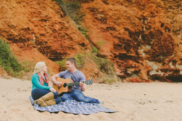ruth and nathan singing and playing guitar against red rock on canadian bay mornington peninsula