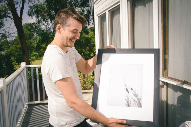 the groom opens his wedding present from his bride an art print of his album cover