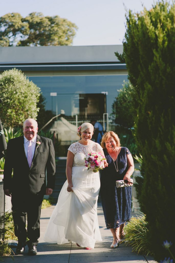Walking down the aisle with both parents at a beautiful Yarra Valley wedding Venue