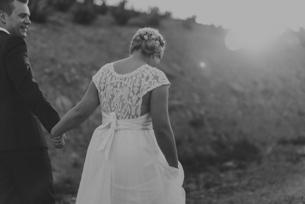 Bride and groom walking along after their ceremony on the lush grounds at Olivigna